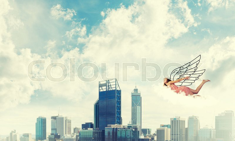 Stock image of 'Young woman flying high in blue sky'