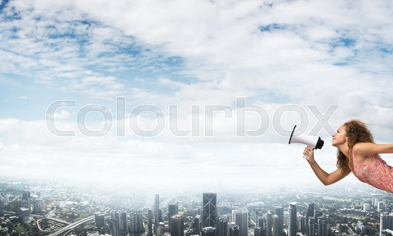 Stock image of 'Young woman in dress making announcement in megaphone'
