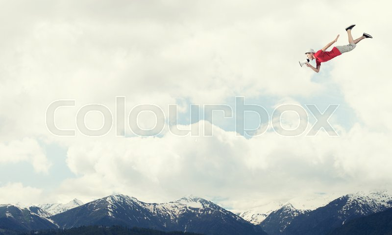 Stock image of 'Young cheerful man with megaphone flying high in sky'