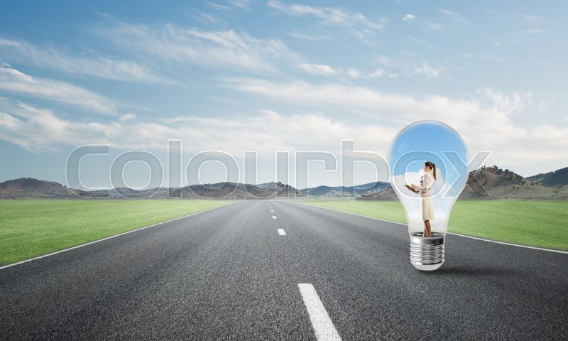 Stock image of 'Young businesswoman trapped inside of light bulb on asphalt road'