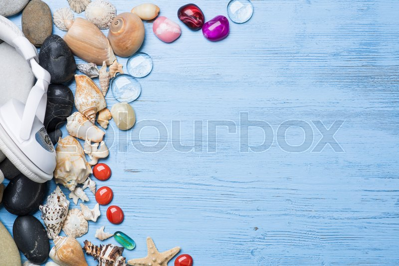 Stock image of 'White headphones among sea shells and stones on wooden surface'