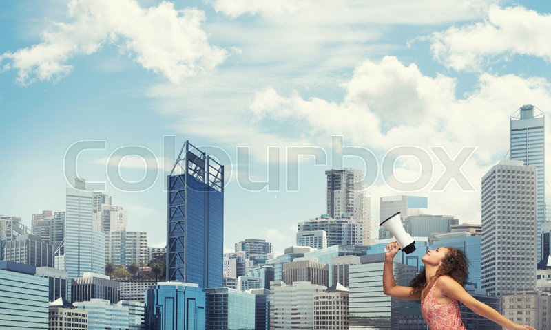 Stock image of 'Young woman against city background screaming emotional in megaphone'