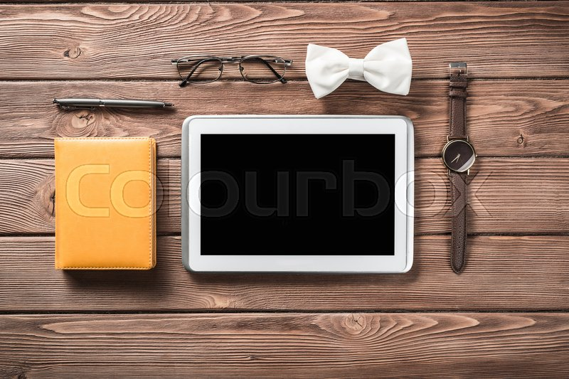 Stock image of 'Tablet pc computer wallet eyeglasses bowtie and wristwatch on table'
