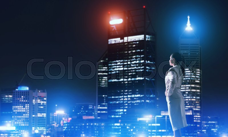 Stock image of 'Rear view of elegant businesswoman viewing lights of night city'