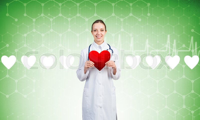 Stock image of 'Young woman doctor against green background holding red heart'