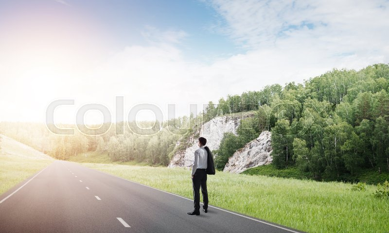 Stock image of 'Elegant businessman on road standing with back and looking ahead'