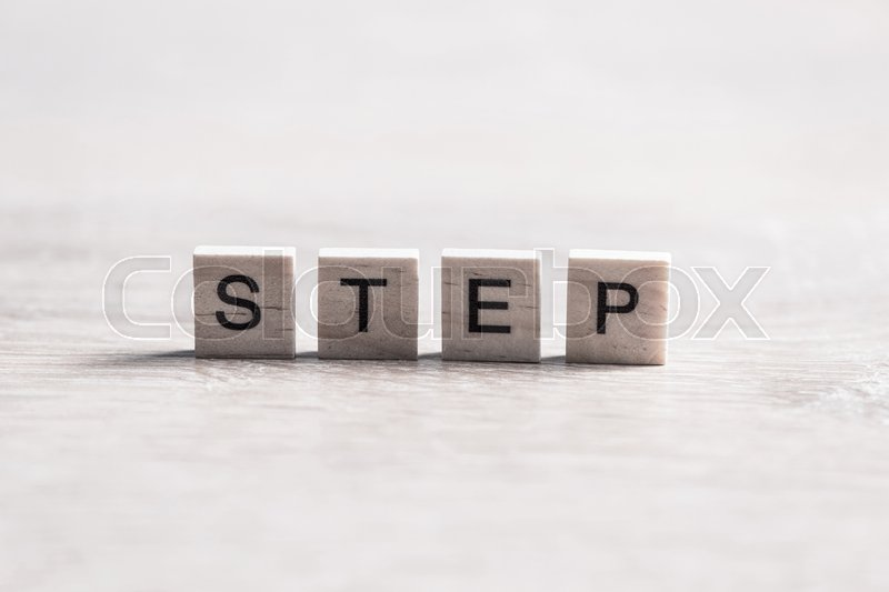 Stock image of 'Alphabet letters on wooden pieces collected word step'