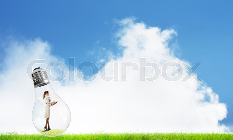 Stock image of 'Businesswoman inside glass light bulb outdoors looking away'