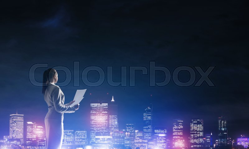 Stock image of 'Rear view of elegant businesswoman with paper sheet against night city'