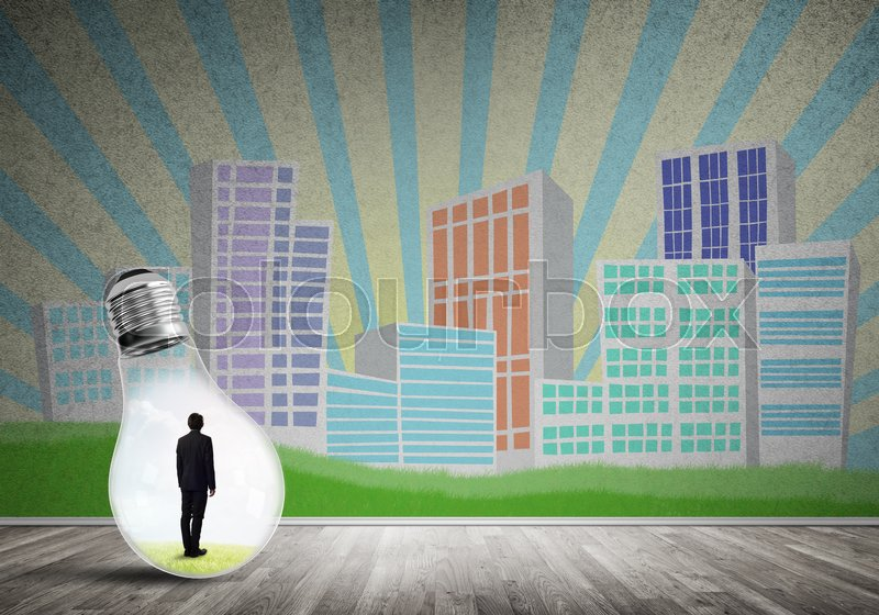 Stock image of 'Businessman inside light bulb against city drawn concept'