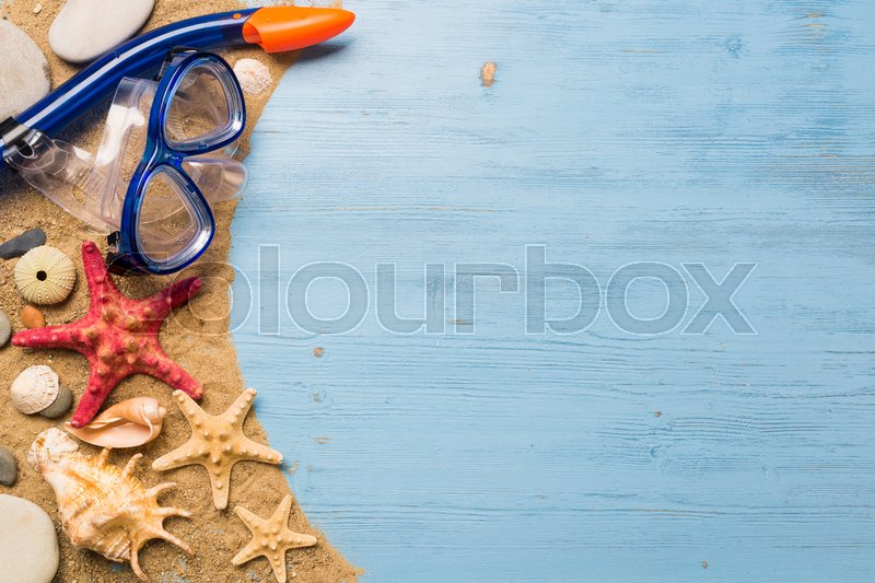 Stock image of 'Diving mask with starfish and shells on blue wooden background'