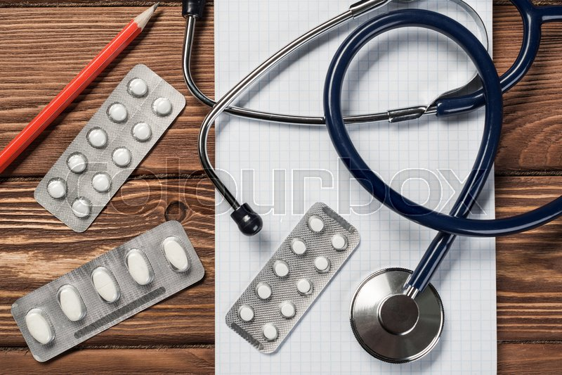 Stock image of 'Close view of stethoscope on wooden desk'