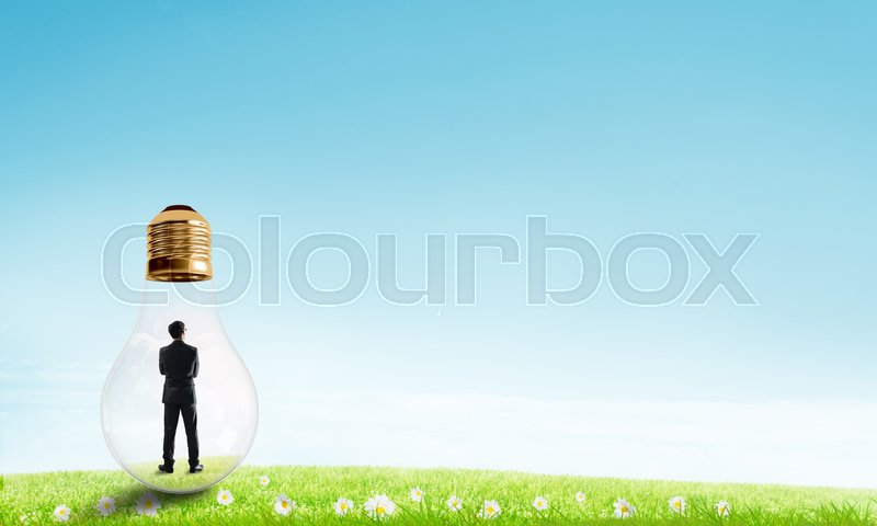 Stock image of 'Businessman inside glass light bulb outdoors looking away'