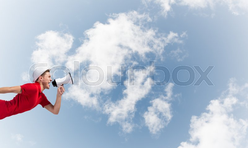 Stock image of 'Young man shouting in megaphone with blue sky background'