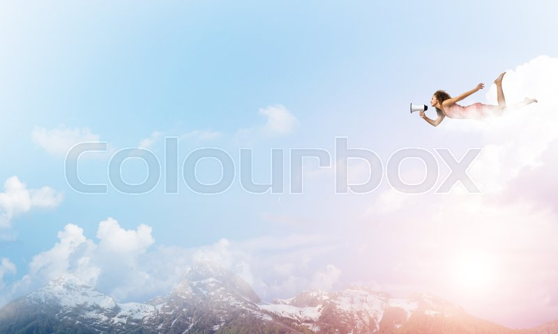 Stock image of 'Young woman with megaphone flying high in sky'