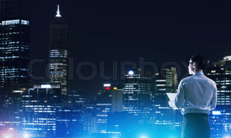 Stock image of 'Elegant businessman with suitcase looking at night city'
