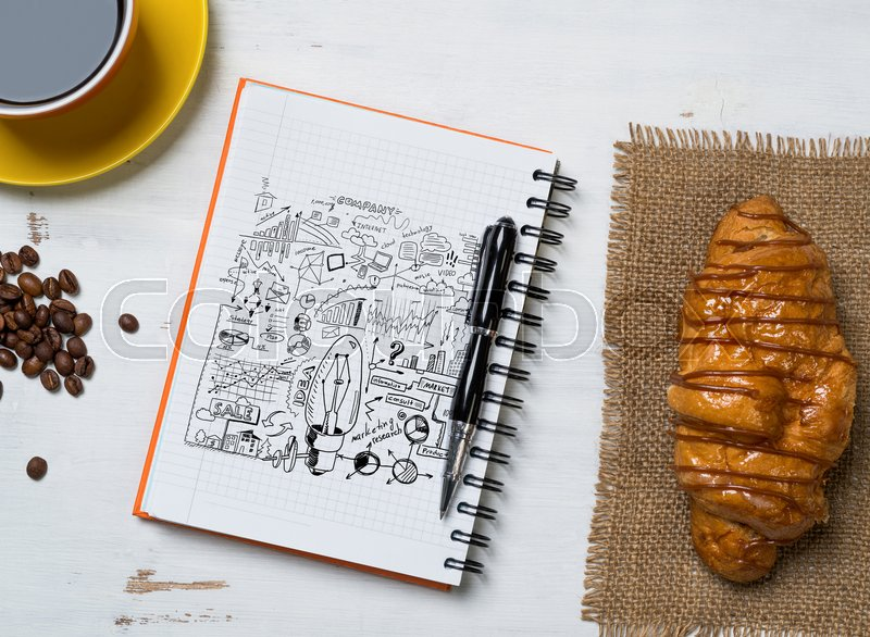 Stock image of 'Notepad with idea sketches coffee cup and pencil on wooden table'
