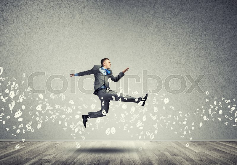 Stock image of 'Young businessman in room running in a hurry'