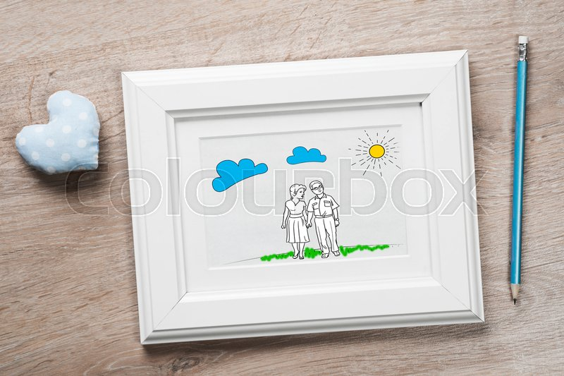 Stock image of 'Photo frame with happy couple drawing on wooden table'