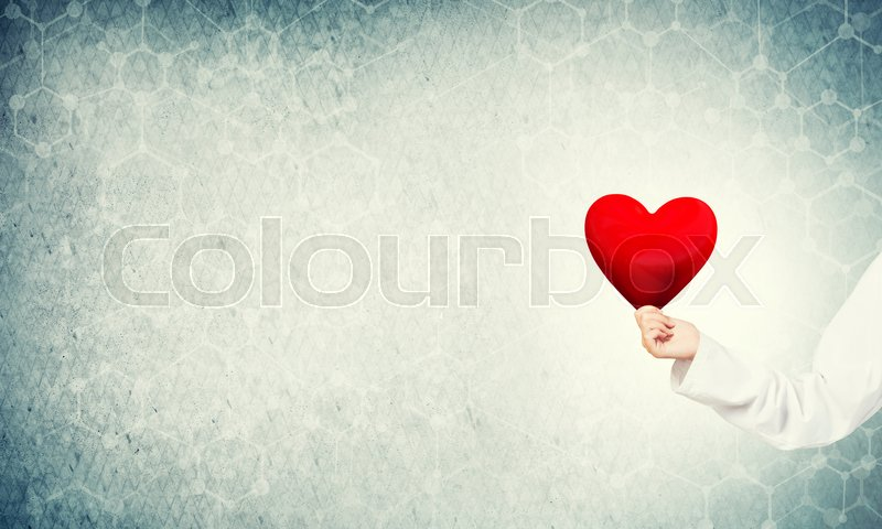 Stock image of 'Hand of woman doctor against blue background holding red heart'