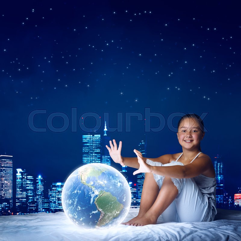 Stock image of 'Cute girl in bed looking at glowing Earth planet. Elements of this image are furnished by NASA'