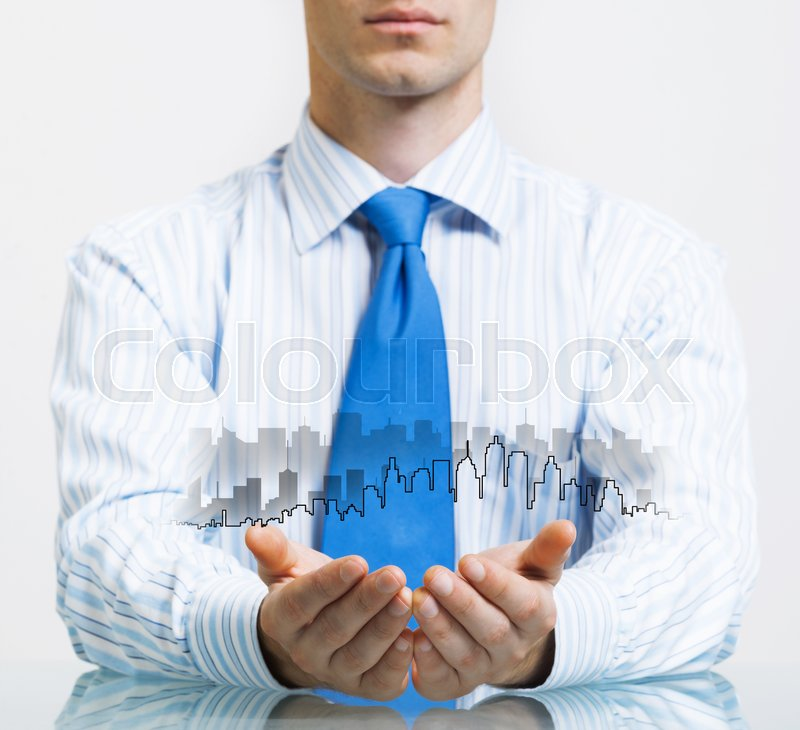 Stock image of 'Businessman sitting at table presenting real estate insurance concept'