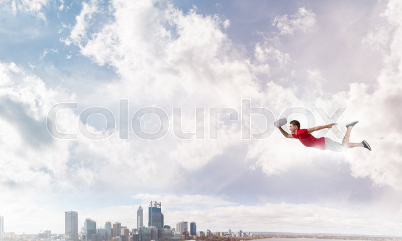 Stock image of 'Young cheerful man flying high above city'