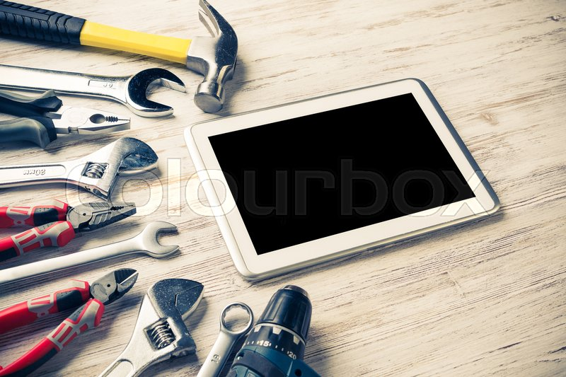 Stock image of 'Set of industrial tools and tablet on wooden surface'