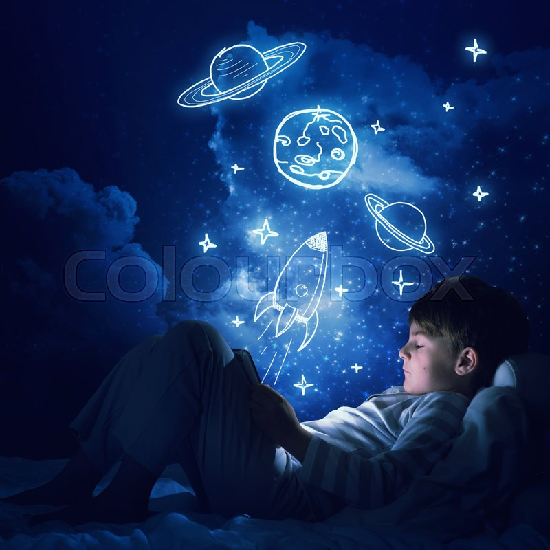 Stock image of 'Teenage boy in pajamas lying in bed using tablet pc'