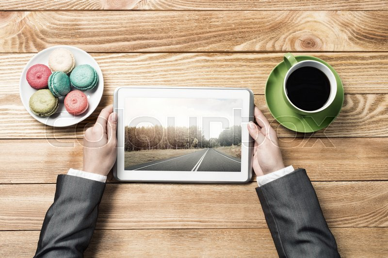 Stock image of 'Top view of businesswoman sitting at wooden table and using tablet pc'