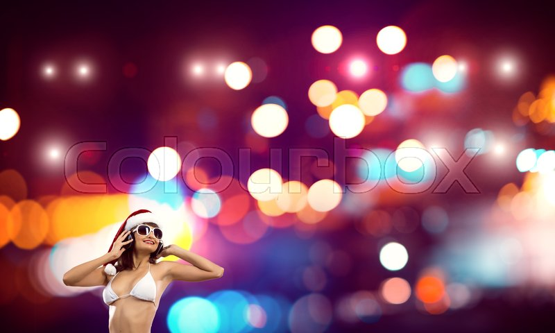 Stock image of 'Beautiful young bikini girl in Santa Claus hat and headphones over bokeh background'