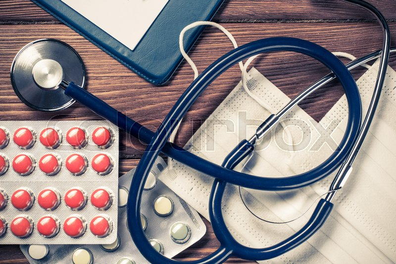 Stock image of 'Doctors wooden table with tablet stethoscope and other stuff'