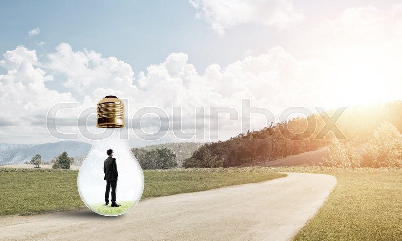 Stock image of 'Young businessman trapped inside of light bulb on countryside road'