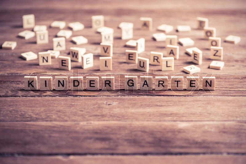 Stock image of 'Alphabet letters on wooden pieces collected to word kinder garten'