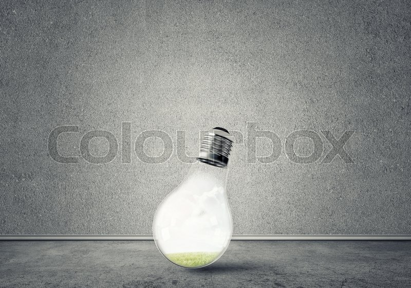 Stock image of 'Glass light bulb in concrete empty room. Eco concept'