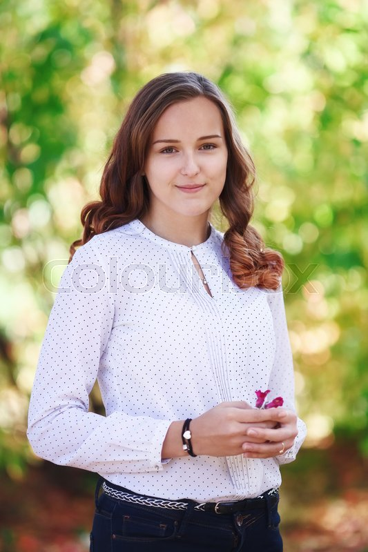 Stock image of 'Young beautiful woman. Beauty smiling teenager girl in autumn park, vertical shoot'