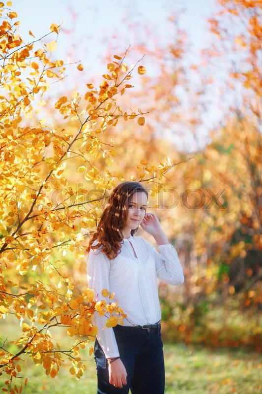 Stock image of 'Young beautiful woman. Beauty smiling teenager girl in yellow autumn park, vertical shoot'