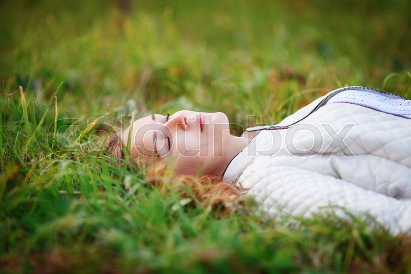 Stock image of 'Young beautiful woman. Beauty girl lying on green grass, closed eyes, close-up'