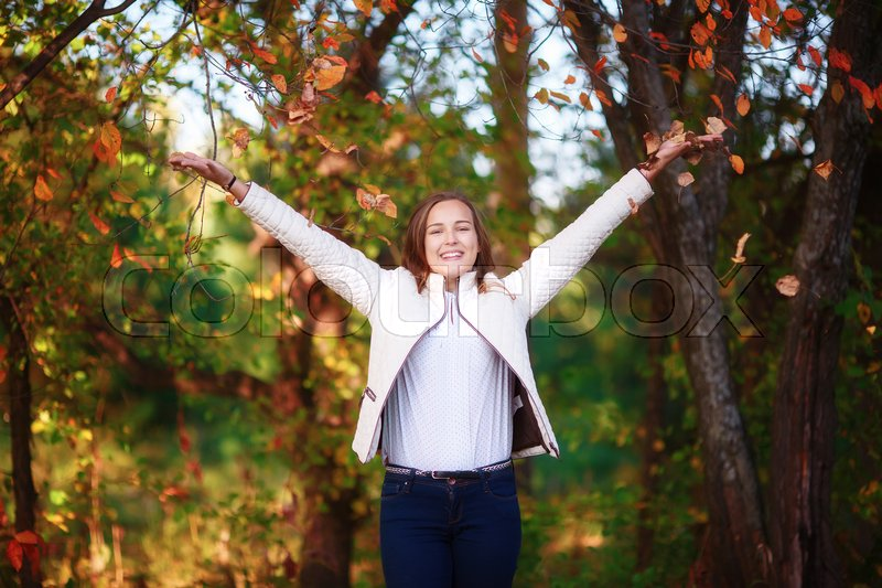 Stock image of 'Young beautiful smiling teenager girl tosses colorful autumn leaves in park'