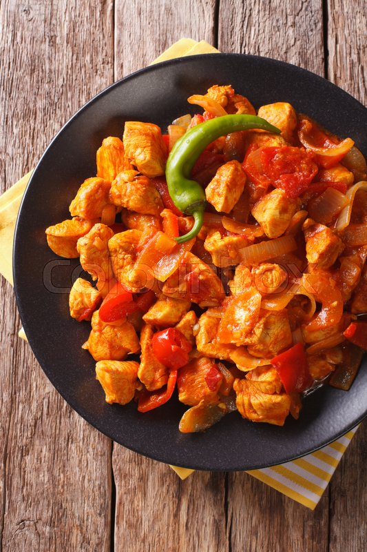 Stock image of 'Chicken Jhalfrazi - indian cuisine chicken with pepper and herbs close-up on a plate. vertical view from above\'