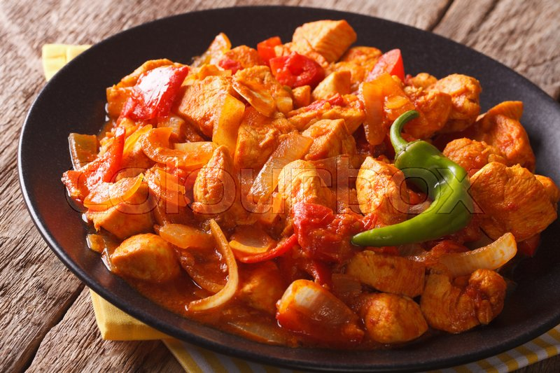 Stock image of 'Spicy chicken jalfrezi with pepper and onion close-up on a plate. horizontal\'