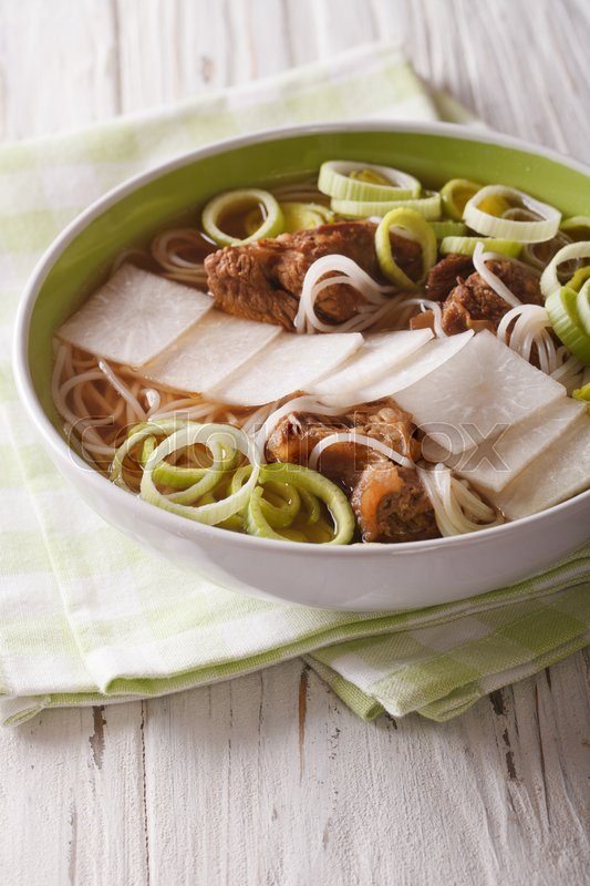 Stock image of 'Korean beef ribs soup, rice noodles, leeks and daikon close up in a bowl. Vertical\'