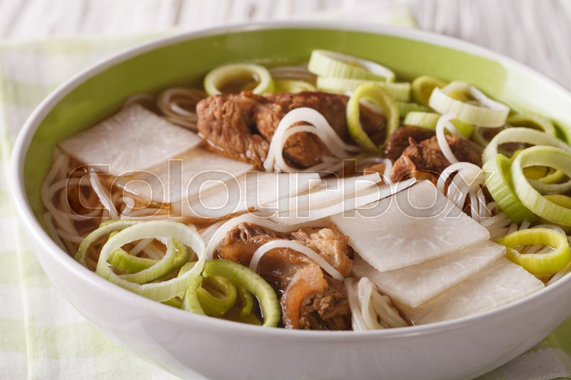 Stock image of 'Galbitang Korean soup with beef ribs, rice noodles and daikon close up in a bowl. horizontal\'