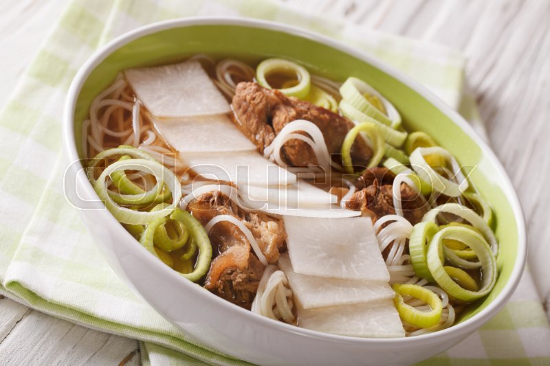 Stock image of 'Korean beef ribs soup, rice noodles, leeks and daikon close up in a bowl. horizontal\'