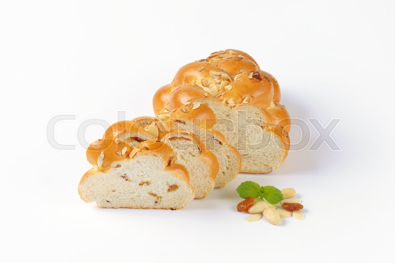 Stock image of 'sliced loaf of Christmas sweet braided bread with almonds and raisins'