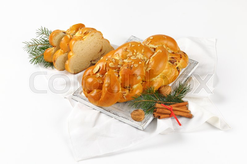 Stock image of 'loaf of Christmas sweet braided bread on wooden cutting board and white napkin'
