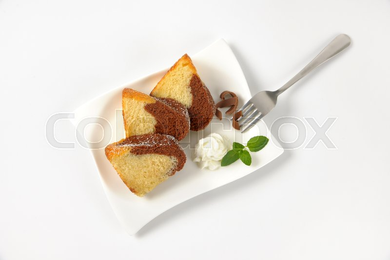 Stock image of 'slices of marble bundt cake and whipped cream on white plate'