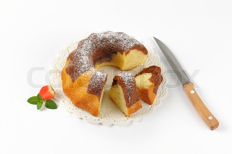 Stock image of 'sliced marble bundt cake on white lace and kitchen knife'