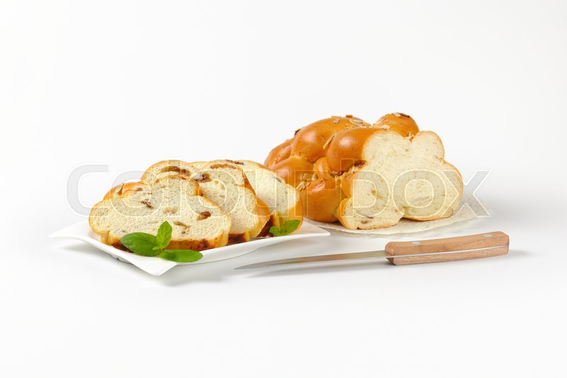 Stock image of 'sliced loaf of sweet braided bread with almonds and raisins'