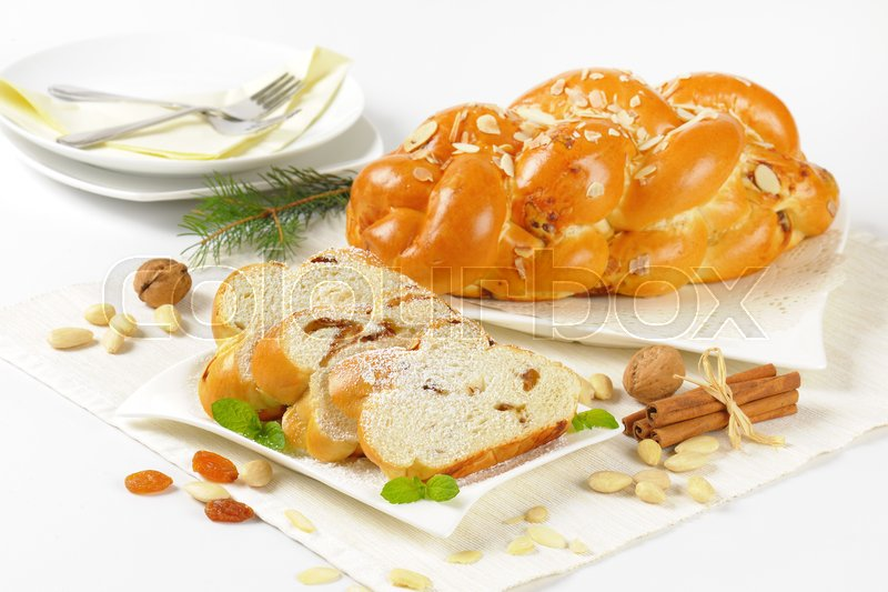 Stock image of 'whole and sliced sweet braided bread with almonds and raisins'